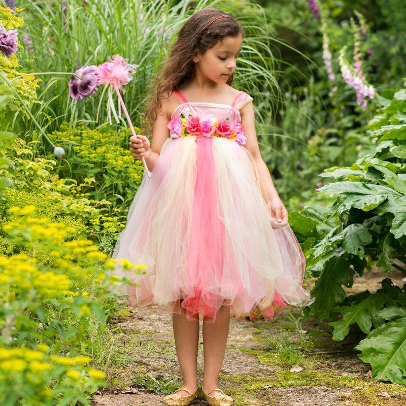 girl wearing a Girls pink and yellow 'Summer Fairy' dress-up costume holding a wand.
