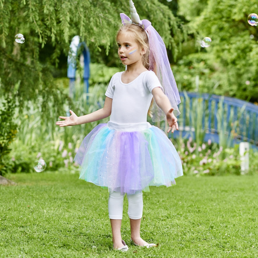 girl wearing a Pastel coloured glittered layers of tulle and feature unicorn horn headband dress up set