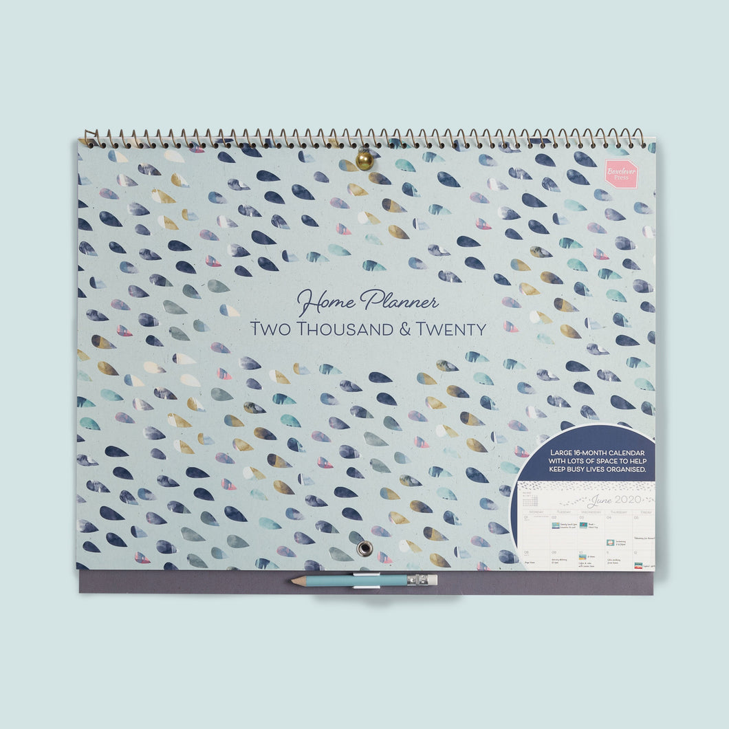 Pale blue Home Planner large wall calendar with tear drop shape watercolour design hanging on a plain blue wall