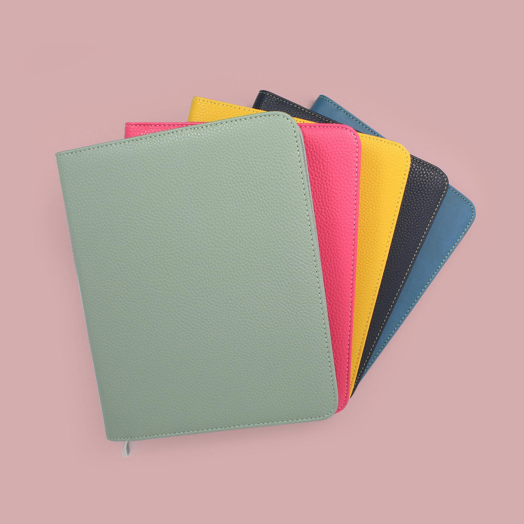 Group of colourful diary covers closed sat on pink background