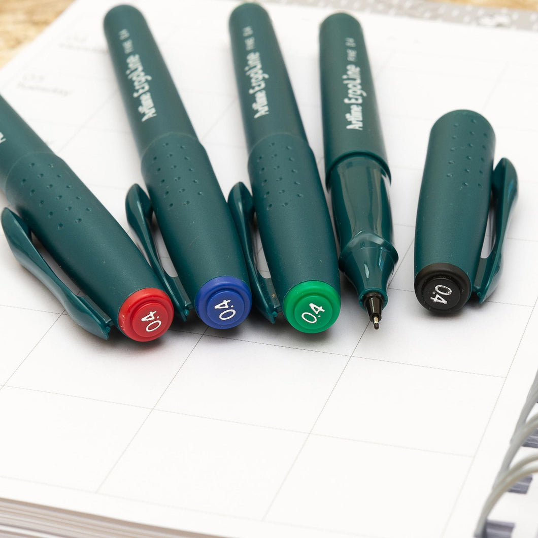 PEN_ERG_Category Selection of nice writing pens with 0.4mm tip in red, blue, green and black on a Family Life Book