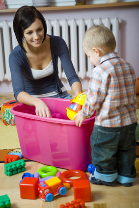 Educator guiding toddler through clean up routine