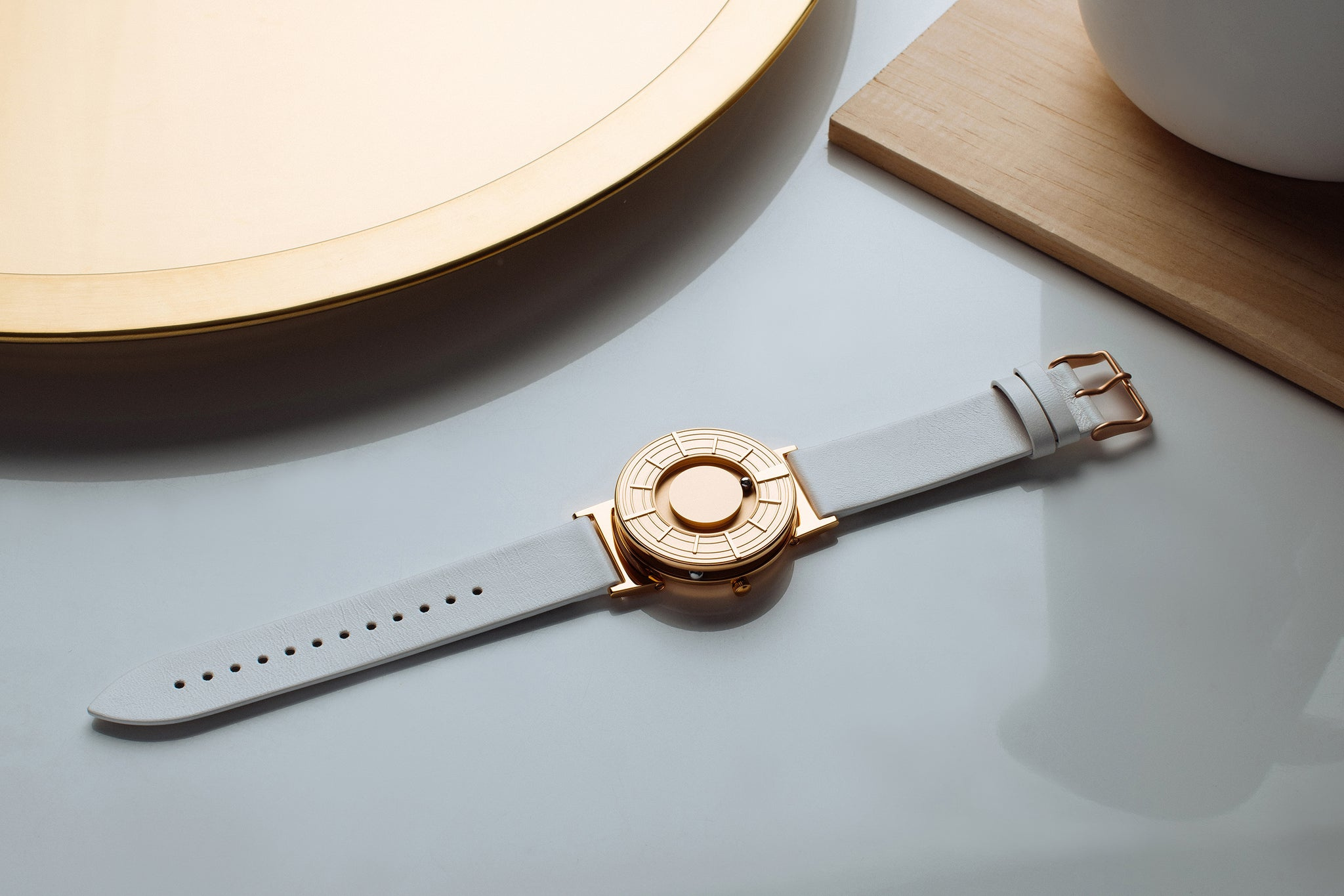 The Bradley Edge Rose Gold is flat on a white glossy surface. There is a round gold disk in the top left corner. There is a square gold object in the top right corner.