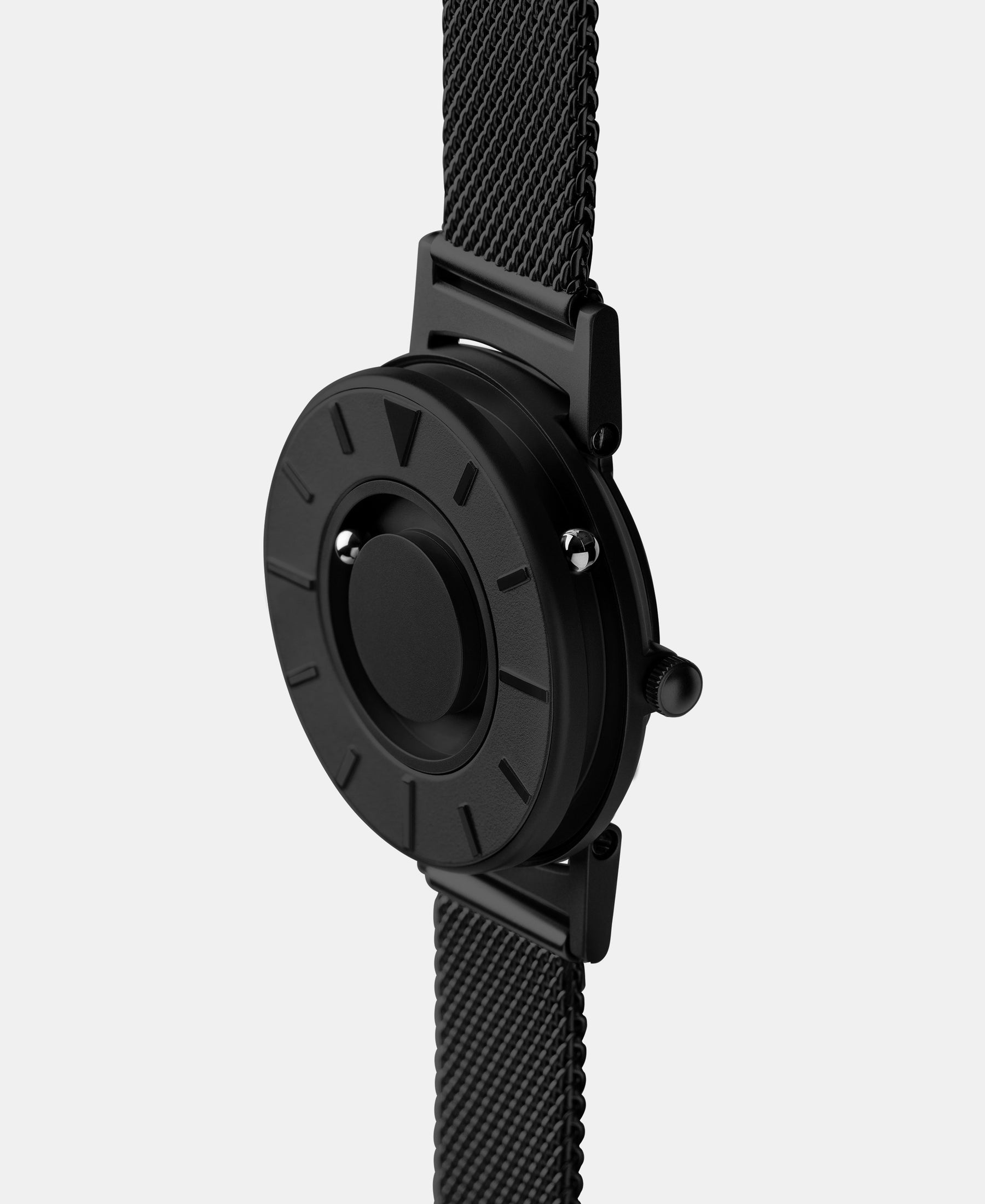 Load image into Gallery viewer, A photo of the watch from a side angle. The recessed track around the outside of the watch face is shown with the hour ball bearing in the track. The raised markers are noticeable from this perspective.