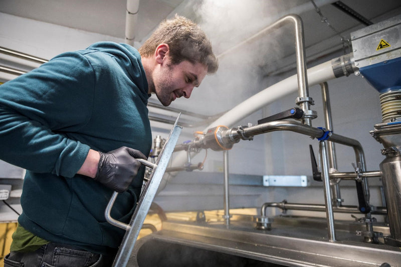 A brewer inspecting the beer as it brews