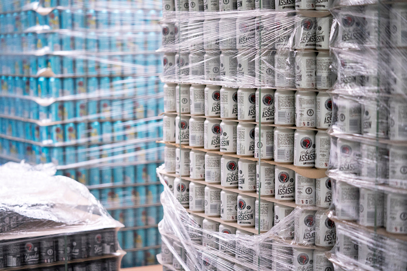 Stacks of craft beer cans including core range IPA Baby-Faced Assassin.