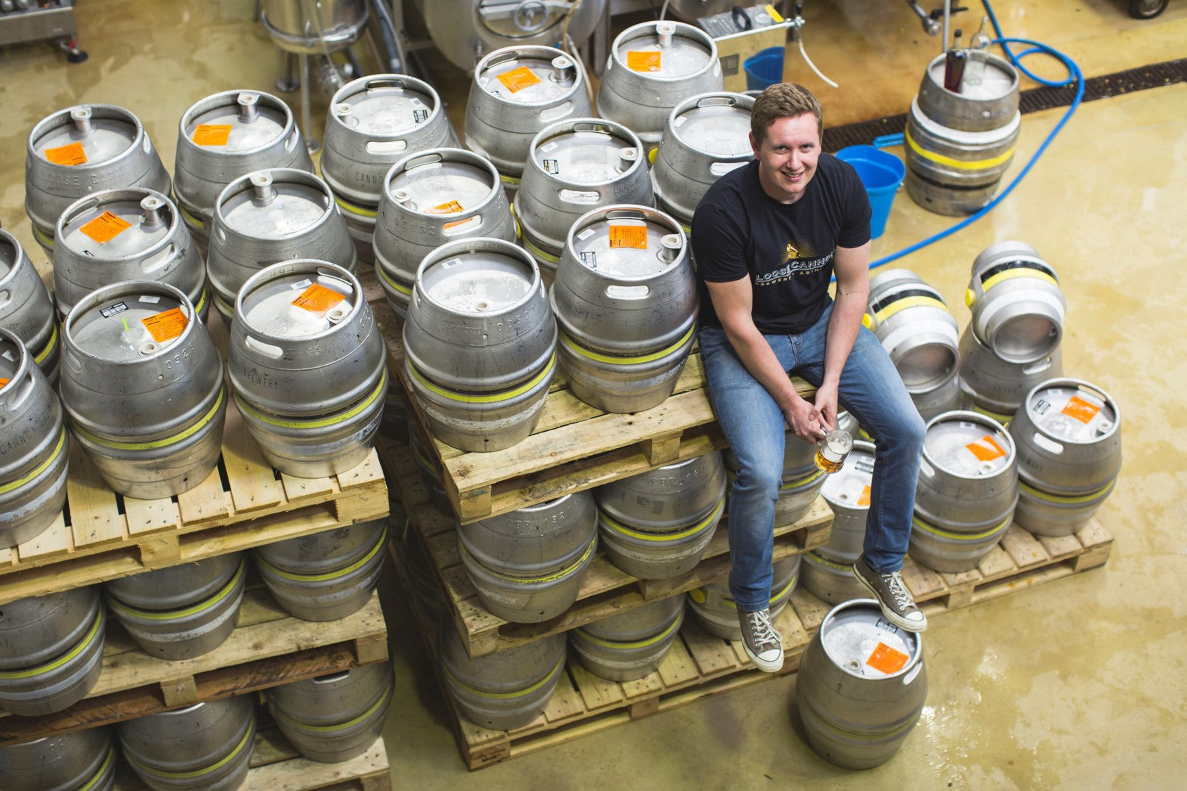 Will Laithwaite sat on barrels at his brewery, Loose Cannon