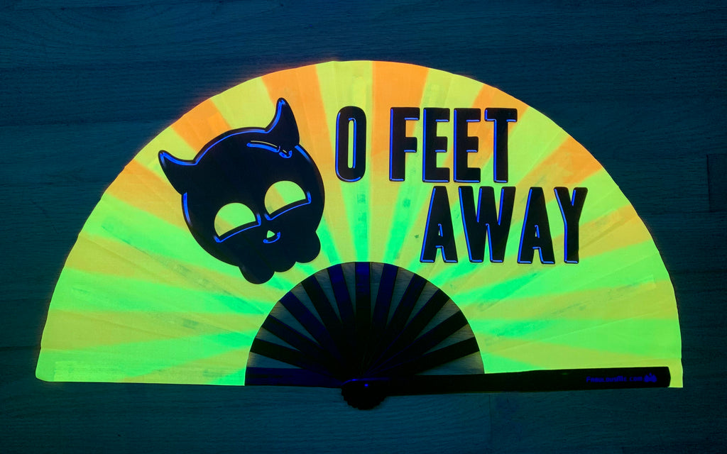 Black print 0 Feet away bamboo hand fan by fabulous me fans on Gold and yellow UV fabric glowing under UV light. For circuit parties, raves, and festivals.