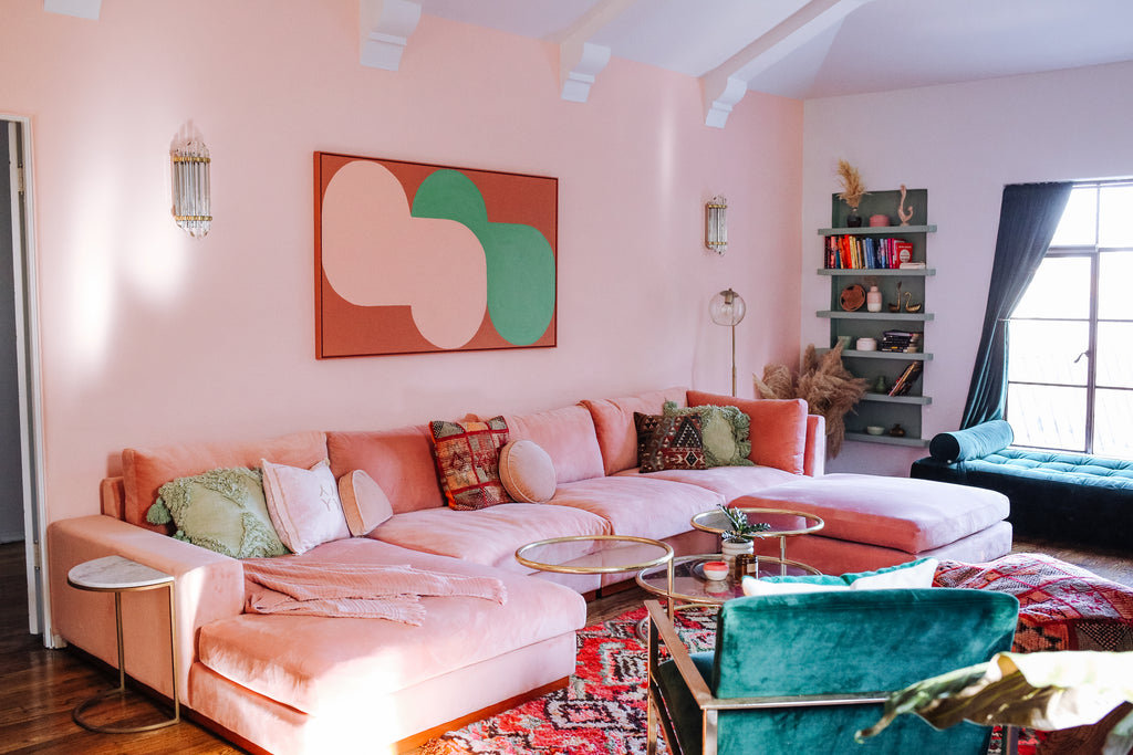 Pink couch in Dazeywood penthouse with decorative throw pillows and pink and green abstract artwork