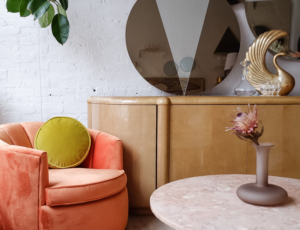 Orange swivel chair with lucite table top, mirror and vase.