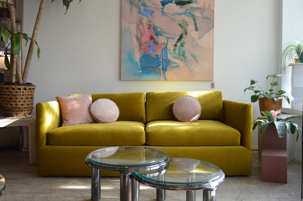 Yellow sofa with abstract art and nesting tables