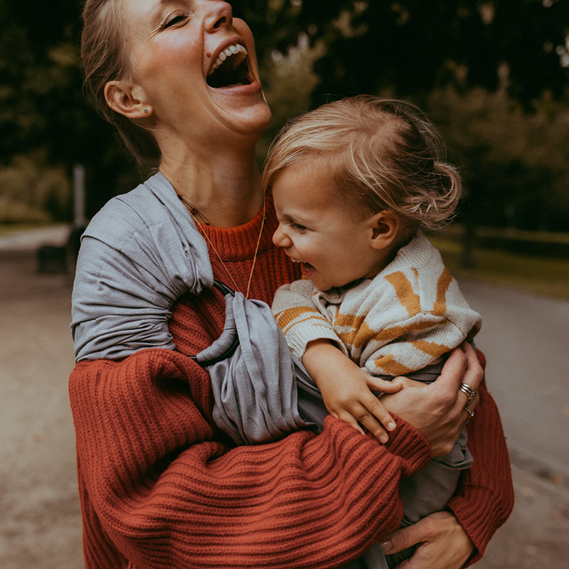 A deep belly laugh with her toddler in her timeless Grey Moon Ring Sling