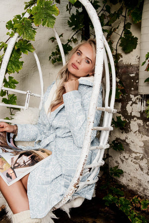 A new bathrobe of True Bandits, hygge robe, with fully embroidered fabric, luxury look. Unique and special, light blue, soft towelling lining. Woman siting in a rocking chair