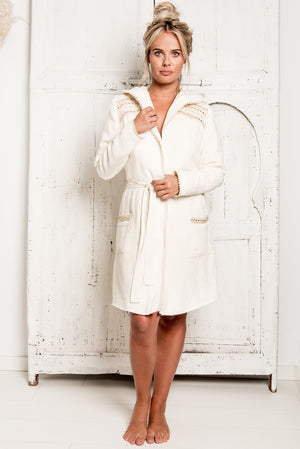 Sexy woman in a beautiful hygge robe, bathrobe of True Bandits. It had nice mirrored details on the shoulders and along the pockets. New ecru bathrobe, unique and special. Soft, stylish and fashionable