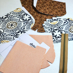 pattern pieces cut from orange pinstripe and medallion brown and white print with zipper all ready to be assembled into Ginger handbag by Sallie Tomato