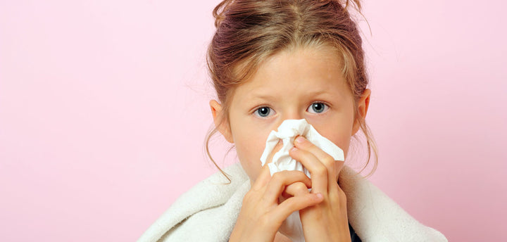 Girl blowing her nose with a tissue