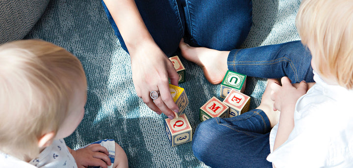 Two kids and a woman playing with blocks