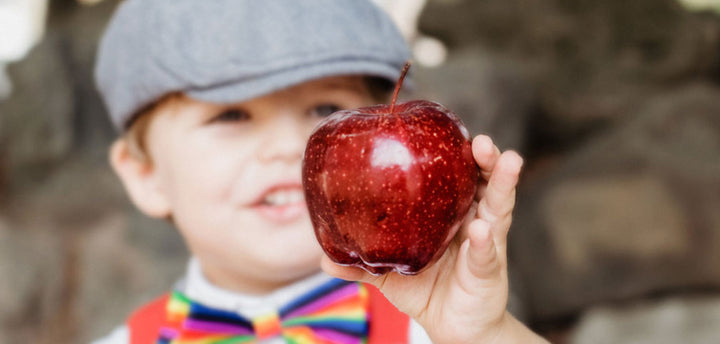 Boy holding a red apple