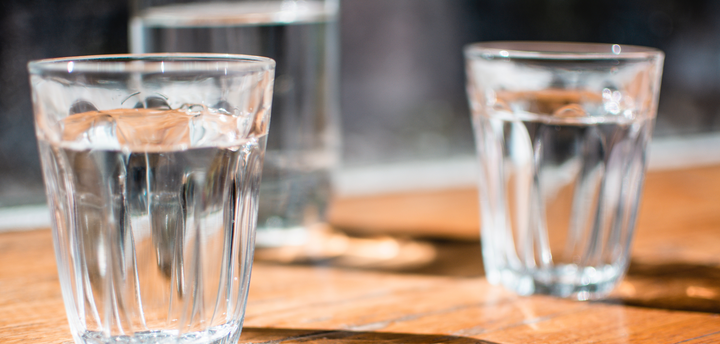 Two glasses of water on a wooden table