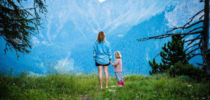 A mother and daughter standing on a mountain