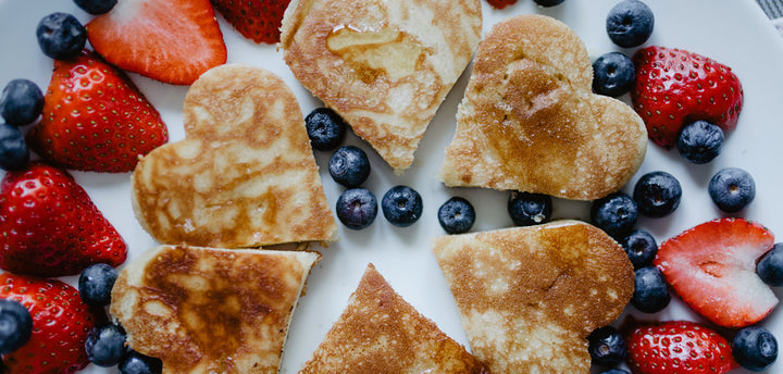 Heart-shaped pancakes surrounded by strawberries and blueberries