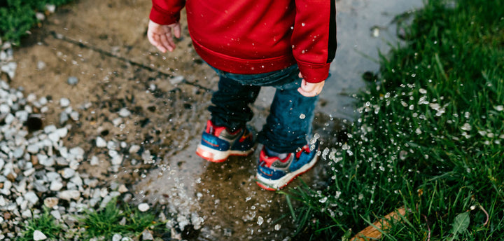 Little boy jumping in a puddle