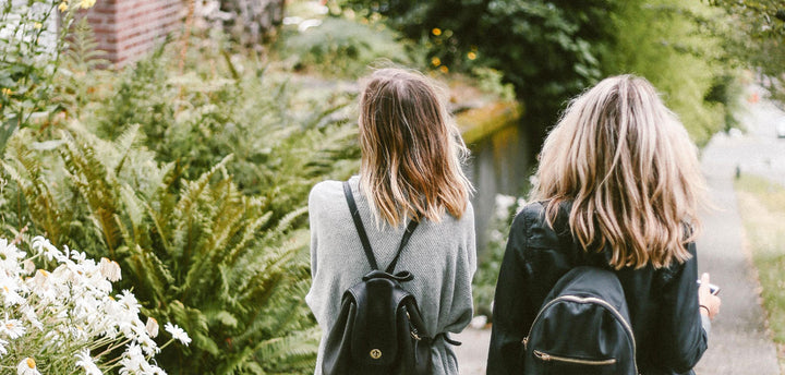 The backs of two female teenagers who are walking down a path