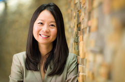 Headshot of Dr. Julie Wei leaning against a brown brick wall