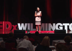 Dr. Julie Wei in a pink dress speaking on the Tedx Wilmington stage