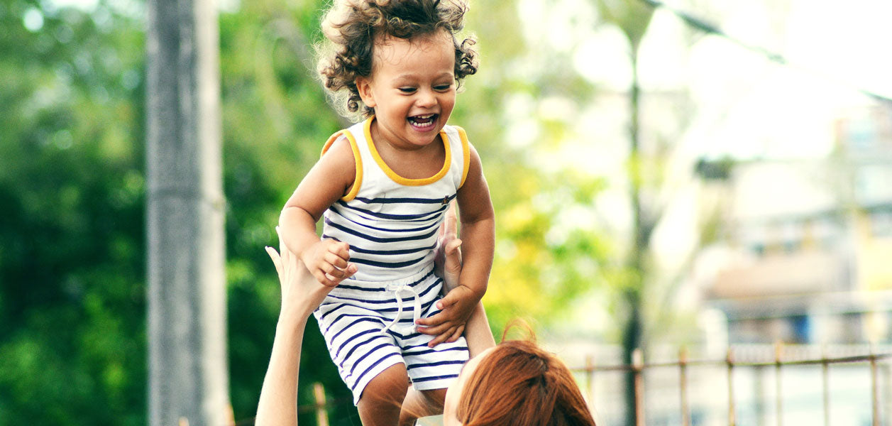 A woman outside throwing a smiling child into the air