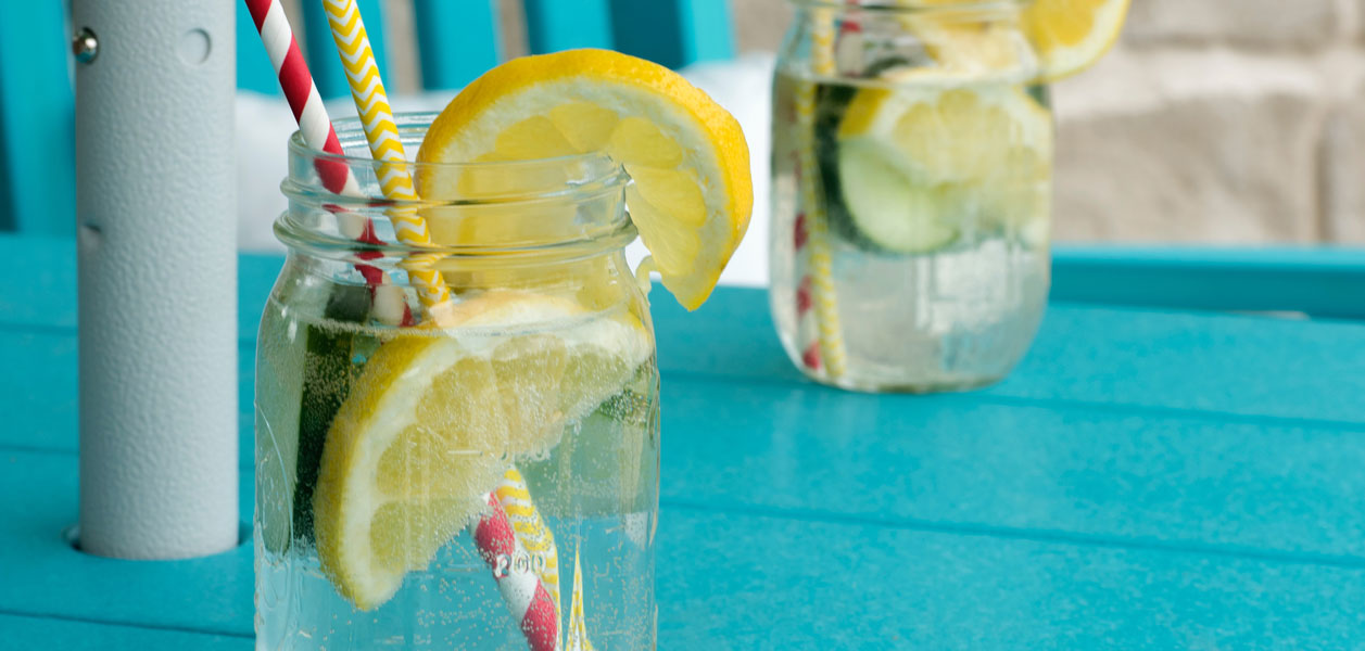 Two mason jars sitting on a blue table outdoors filled with sparkling water, lemons and cucumbers and two straws each