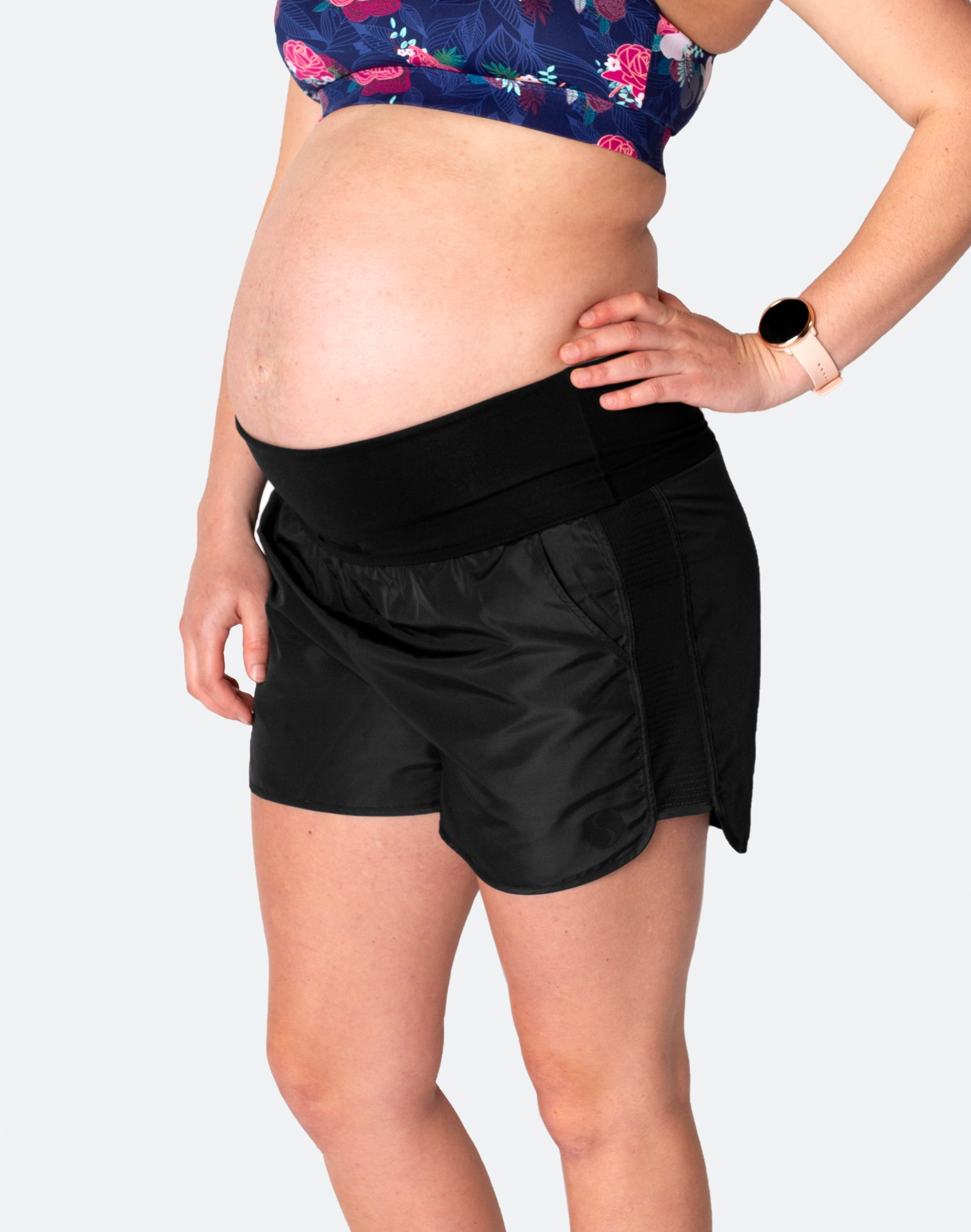 pregnant woman wearing high waisted running shorts folded under the bump
