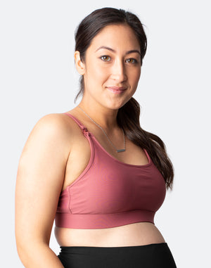 Pregnant woman wearing a rouge breastfeeding bra and black leggings