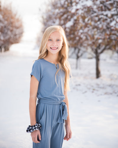 The Brielle jumpsuit for tweens and teens features comfy, stretchy fabric, elastic and tie waist, front pockets, and an accent zipper at the neck.  Feels like pajamas, looks like a million bucks!