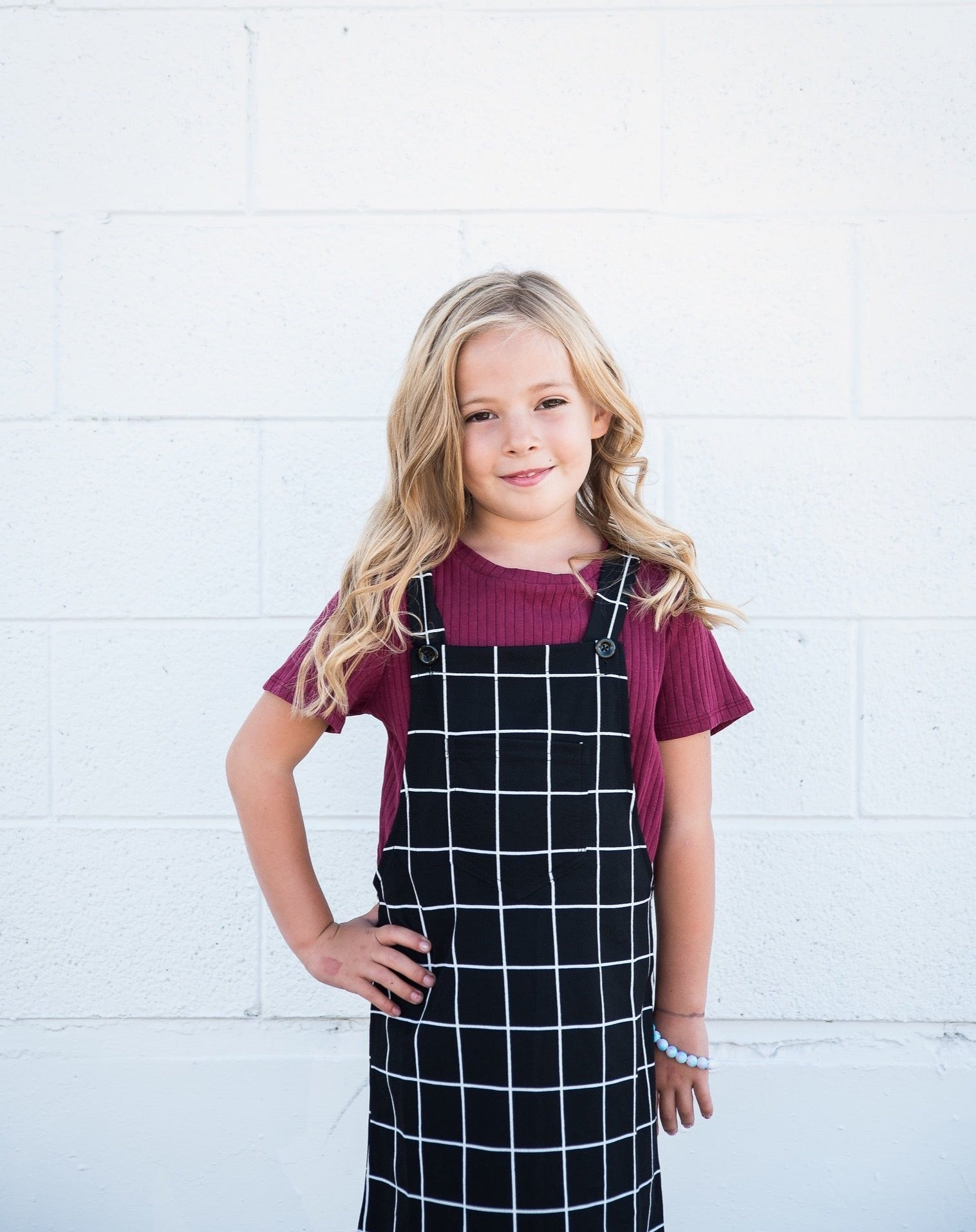 Bib Pocket Overall dress with classic windowpane checks.  This jumper is a customer favorite! Pair it with a white or yellow top, or the burgundy tee featured, and you have a classic outfit that you'll love for years to come.