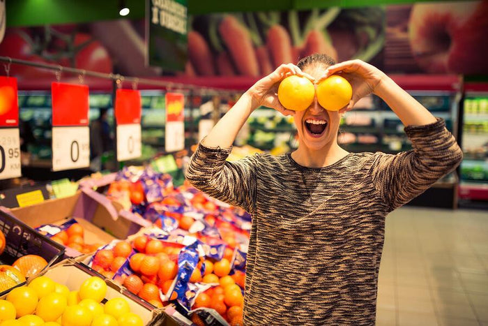 women holds oranges over her eyes at supermarket