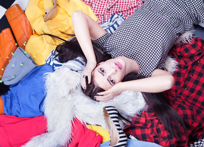 women lays in a pile of clothes with her hands on her head
