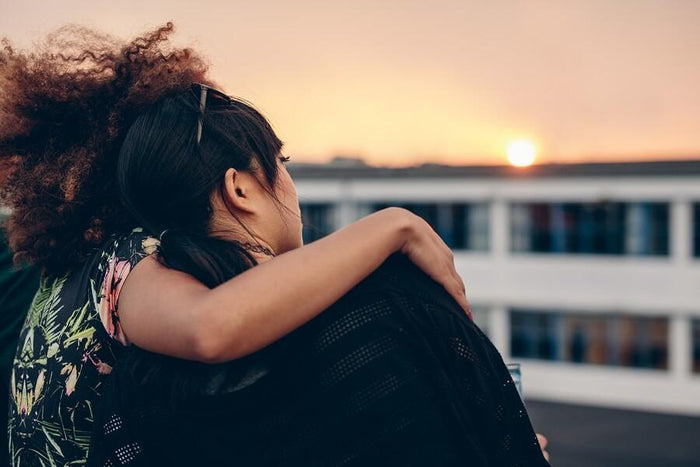women being comforted on a rooftop during sunset