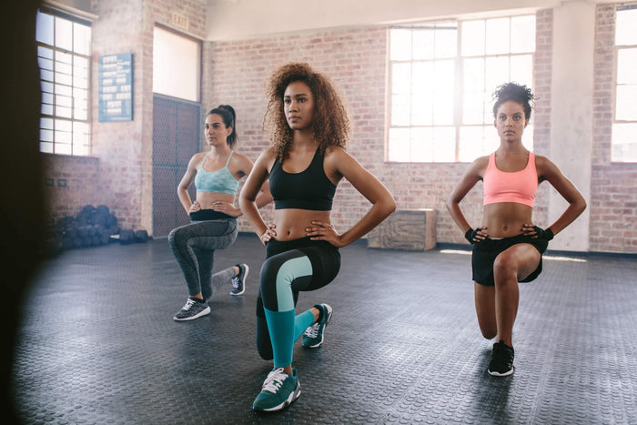 women doing lunges together in a fitness studio