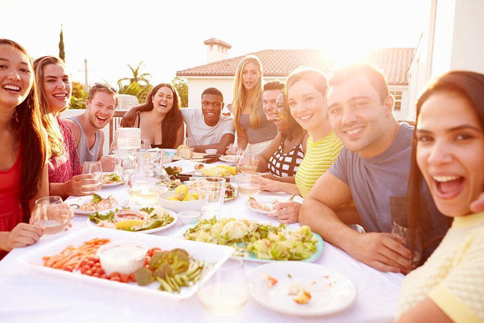 friends eat together around a large table outside
