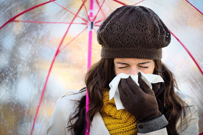 women sneezes while dressed for winter