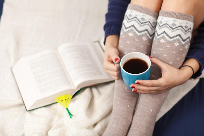 women in tall socks drinks coffee while reading a book