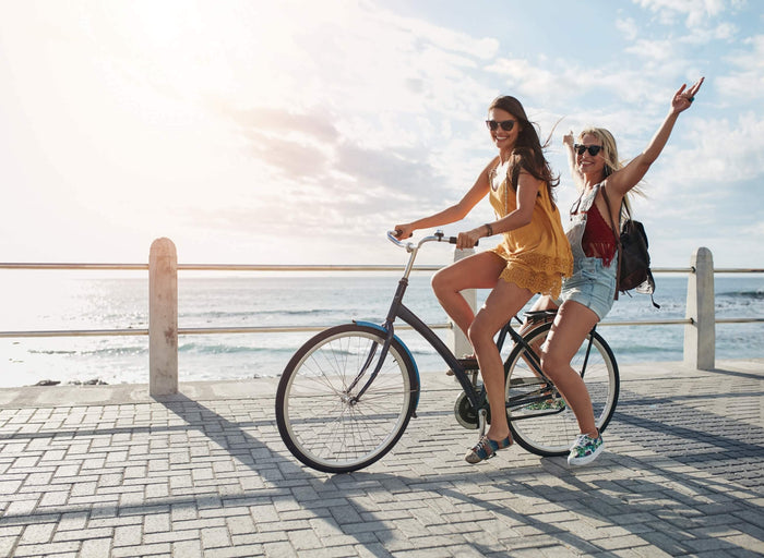 two women ride a bike together on a pier