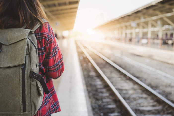 women waits for train with her backpack on