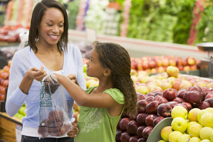 mom and daughter find fresh produce at a supermarket