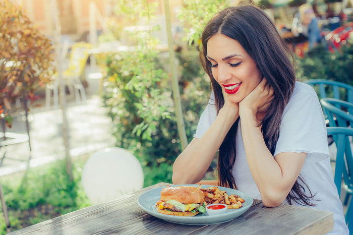 women eats a burger and fries on a blue plate with ketchup