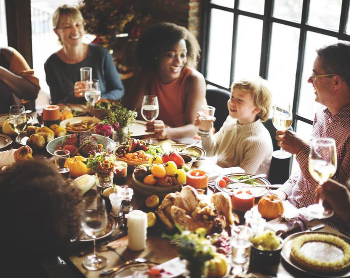 family gathers around the table for thanksgiving