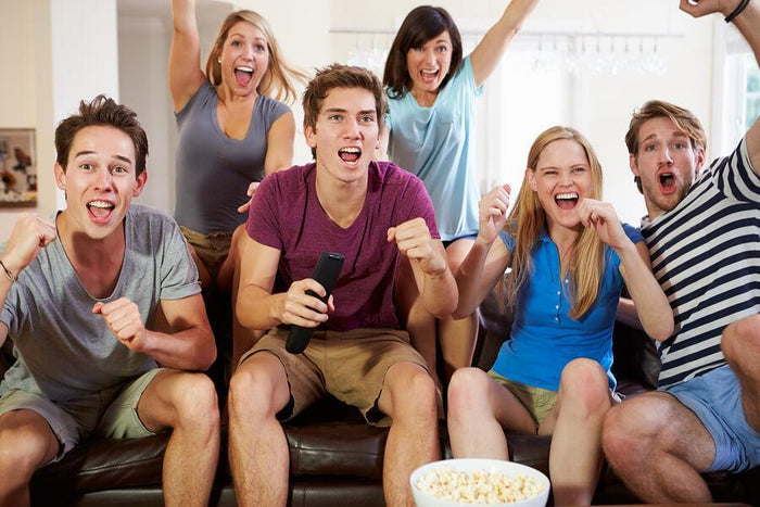 group of friends cheers towards a television