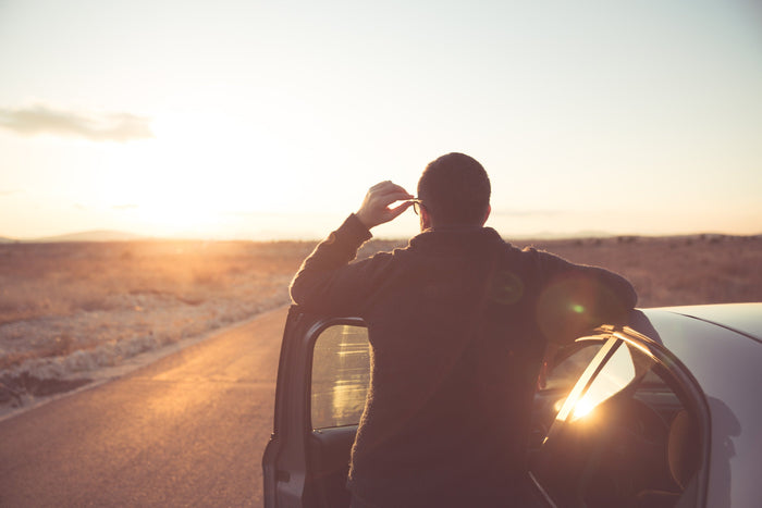 man stands outside of his car during sunset