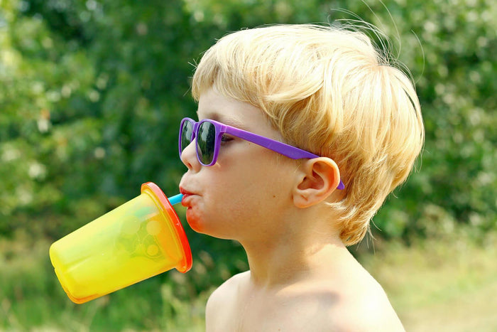 kid drinking from a cup on a summer day